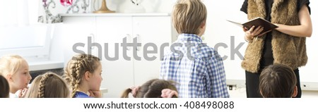 Shot from the back of the classroom of a schoolboy standing in front of his teacher - stock photo