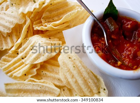 Shot from the top down potato chips with fresh salsa bright
