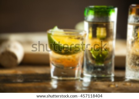 Shot glass of tequila on wood table background with blur applied to image.