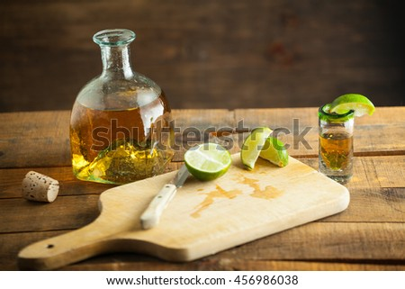 Shot glass of tequila with bottle. Selective focus. Blurred background. - stock photo
