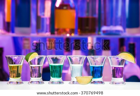 Shot glasses with lime in row, bar bottles on back - stock photo