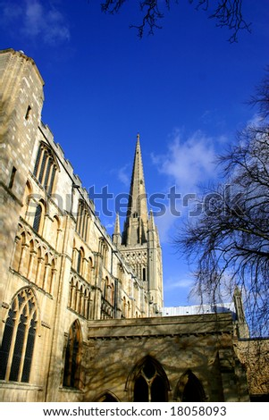 Shot looking up at the spire of Norwich Cathedral against a clear blue sky beyond - stock photo