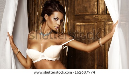 Shot of a beautiful and sexy girl with jewelry wearing white lingerie, looking at camera. - stock photo
