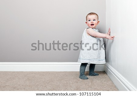 Shot of a Beautiful Baby Girl against Wall - stock photo