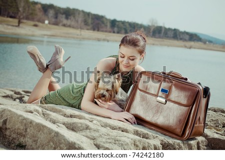 Shot of a beautiful girl  lying on the shore of the lake with a suitcase and a dog (Yorkshire terrier) - stock photo