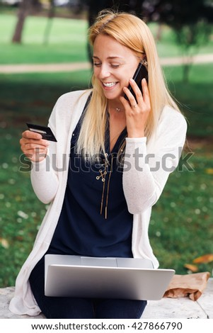 Shot of a beautiful woman doing some online shopping in the park  using her laptop. Change the way you shop with modern technology  - stock photo