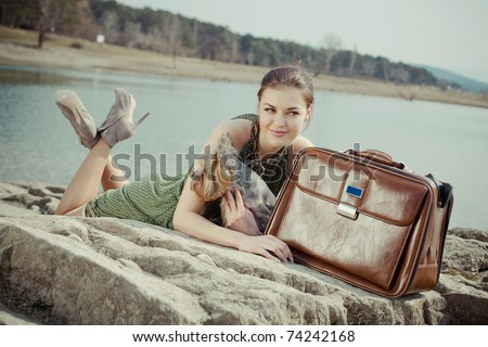 Shot of a beautiful woman lying on the shore of the lake with a suitcase and a dog (Yorkshire terrier) - stock photo
