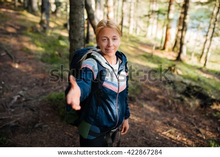 Shot of a beautiful  young woman offering you a hand while hiking  - stock photo