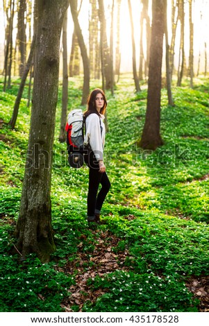 Shot of a beautiful young woman with a backpack standing in a spring forest