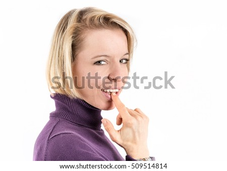 Shot of a blonde woman putting her finger in her mouth in front of a white background
