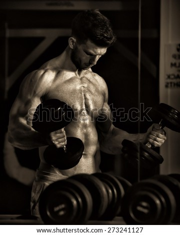 Shot of a Bodybuilder lifting dumbell in dramatic gym lighting