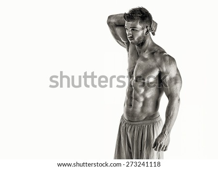 Shot of a bodybuilder posing on white background - stock photo