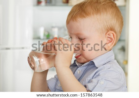 shot of a boy drinking a glass of water - stock photo
