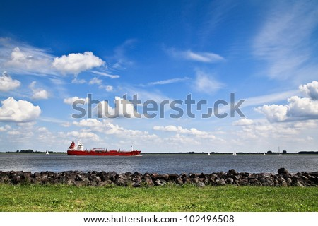 Shot of a cargo ship on the river Elbe with a beautiful sky. - stock photo