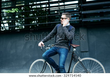 Shot of a casual dressed businessman taking a break and using cell phone while going to the work. - stock photo