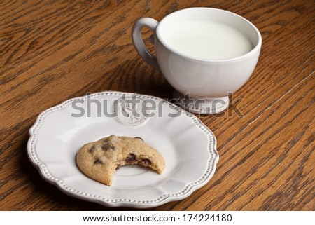 Shot of a chocolate chip cookie with a bite taken out of it on a wooden table - stock photo