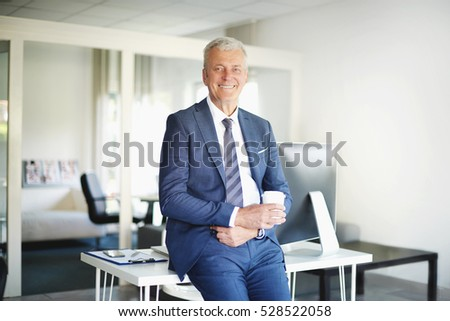 Shot of a confident senior businessman standing in the office while looking at camera and smiling.