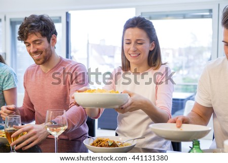 Shot of a couple at a dinner party. They are smiling and passing around the food - stock photo