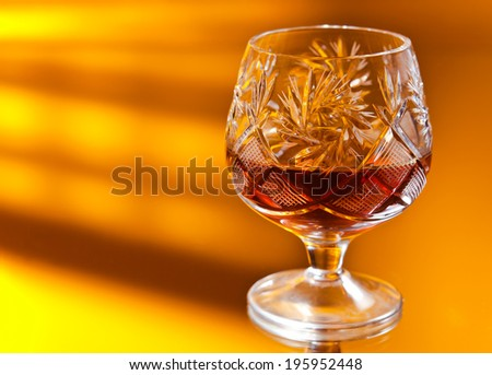 shot of a cut crystal glass on mirror table - stock photo