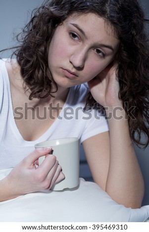 Shot of a depressed young woman holding a mug