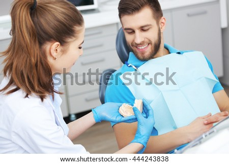 Shot of a female dentist explaining  to young male patient how to properly brush his teeth. - stock photo