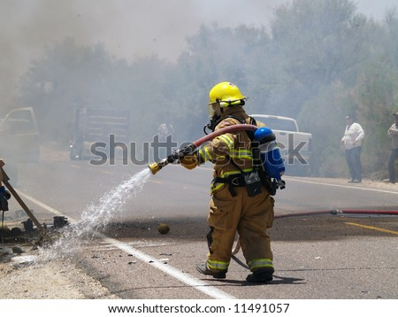 Shot of a firefighter dousing a burning truck on the road.