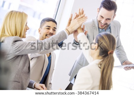 Shot of a group of colleagues high-fiving each other during an informal meeting.Happy business team celebrating good news. - stock photo