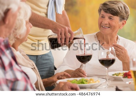 Shot of a group of elderly people drinking wine on a dinner party