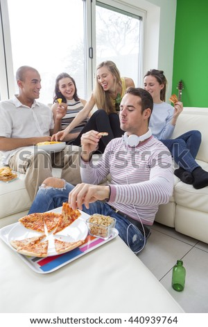Shot of a group of friends enjoying pizza together at home. - stock photo