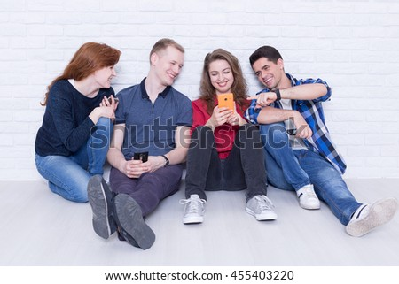 Shot of a group of young people sitting on a floor and laughing