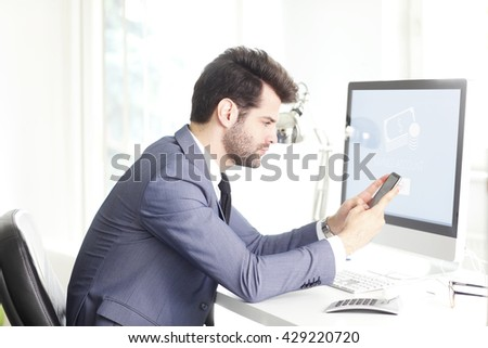 Shot of a handsome businessman using mobile phone while sitting at desk in front of computer and working at office.