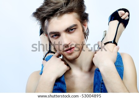 Shot of a handsome man holding woman's legs in elegant shoes. - stock photo