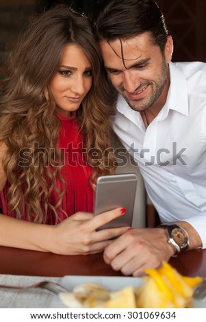 Shot of a happy couple looking on a phone. - stock photo