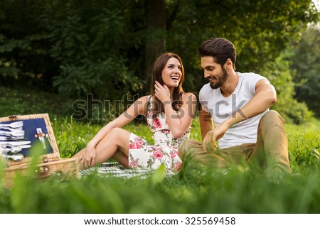 Shot of a happy young couple having romantic time and enjoying a summer picnic. Natural light, selective focus. - stock photo