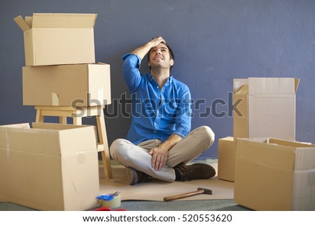 Shot of a happy young man sitting in the room surrounded by cardboard box after moving his new home.