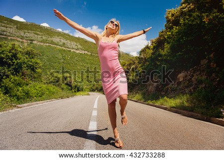 Shot of a happy young woman enjoying a road trip. - stock photo