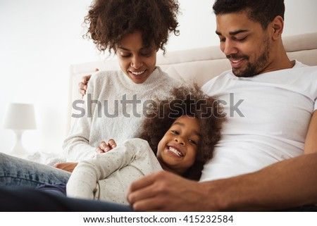 Shot of a laughing little girl lying in bed with her parents in the morning. - stock photo