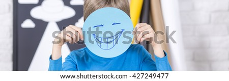 Shot of a little boy covering his face with a drawing of a smiling face