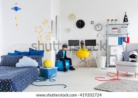 Shot of a little boy in his space themed bedroom - stock photo