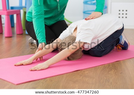 Shot of a little boy stretching on an exercise mat and his physiotherapist helping him