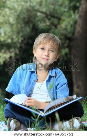 Shot of a little boy with a book having a rest outdoor.