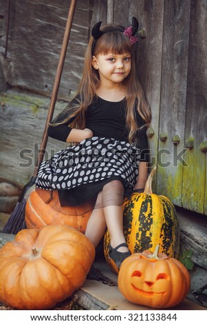 Shot of a little girl in halloween costume posing with pumpkins during Halloween party - stock photo