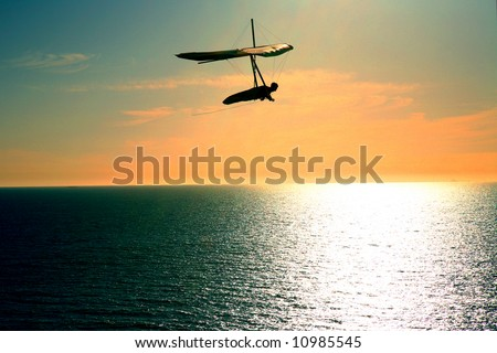 Shot of a man hang gliding in Northern California over the beach.