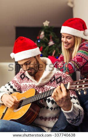 Shot of a man playing a guitar for his girlfriend. - stock photo