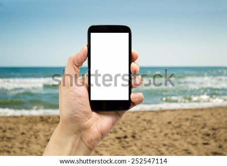 shot of a man's hand holding a smartphone on the beach - stock photo