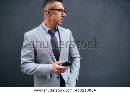 Shot of a mature businessman with cell phone in his hands outside