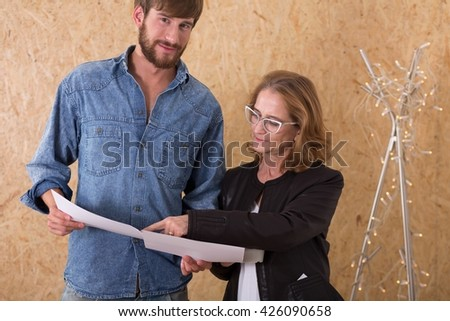 Shot of a middle-aged woman talking to a young man while showing him some papers, both standing against the chipboard wall - stock photo