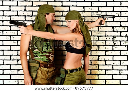 Shot of a military couple posing against brick wall. - stock photo