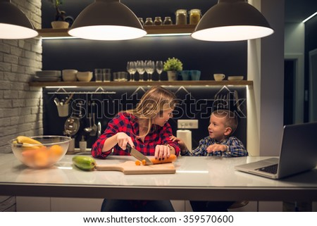 Shot of a mother and son preparing dinner. - stock photo