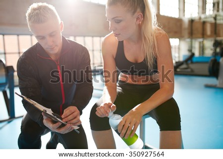 Shot of a personal trainer helping a gym member with her exercise plan. Trainer goes through fitness plan with client in the health club. - stock photo